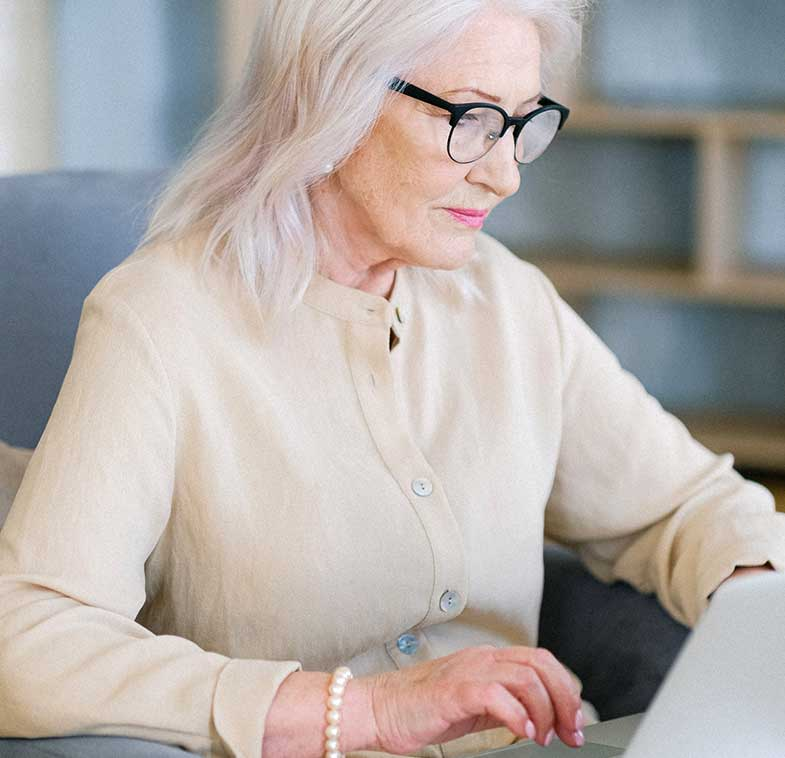 Aged Woman in Eyeglasses Surfing the Internet on a Laptop