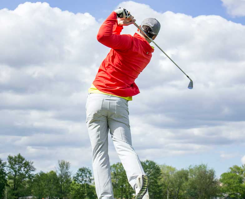 Man with Red Jacket Taking Golf Swing