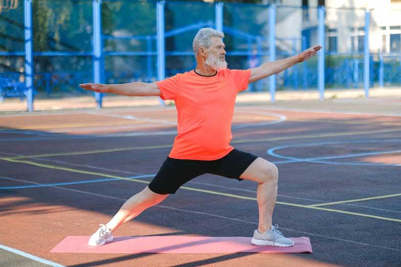 Senior Person in Orange Shirt Doing Yoga