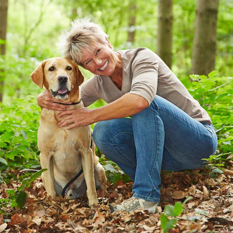 Smiling Senior Woman with a Dog in a Forest